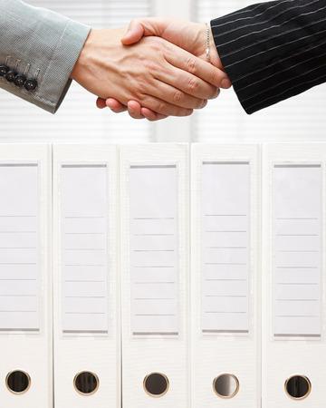 zakenman en zakenvrouw handen over documenten van de vennootschap schudden