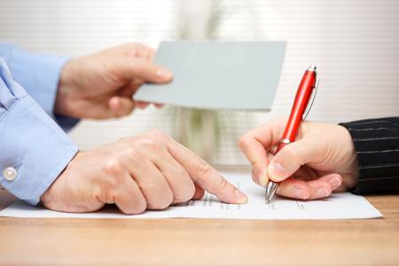 Arbeitgeber zeigt Mitarbeiter, wo ihre Broschüre zur gleichen Zeit zu unterzeichnen und geben