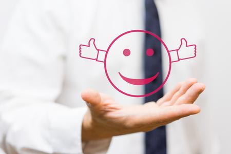 Geschäftsmann hält den Smiley mit Daumen nach oben