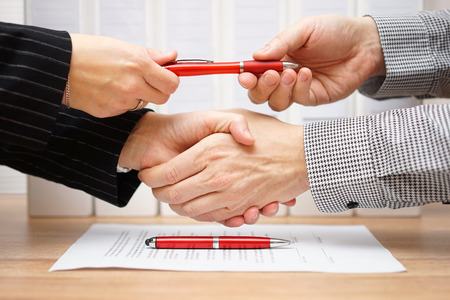 Business partners shaking hands and exchanging pen after finished deal