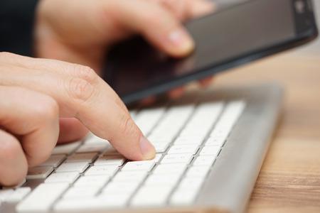 Nahaufnahme von jungen Erwachsenen auf Computer arbeiten und smart mobile zugleich mit