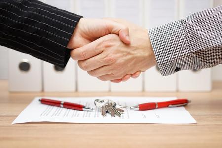 client en agent zijn handshaking over een onroerend goed contract en sleutels Stockfoto
