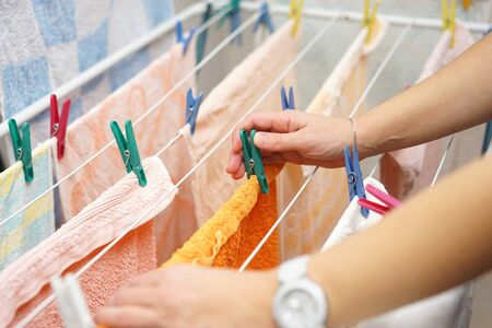 hanging up: midsection of woman hands  hanging up laundry Stock Photo