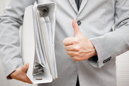Businessman is holding document binders and showing thumbs up gesture