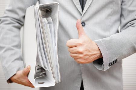 Zakenman houdt document bindmiddelen en het tonen van thumbs up gebaar Stockfoto