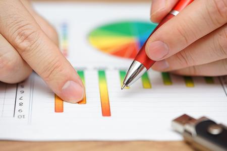 Close-up van zakenman analyseren van bedrijfsgegevens op grafieken en diagrammen