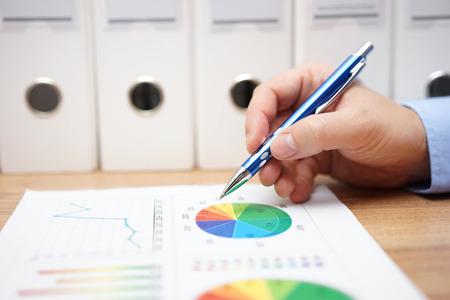 Nahaufnahme des Mannes Hand Geschäft verschiedene Finanzdiagramme auf dem Tisch zu analysieren