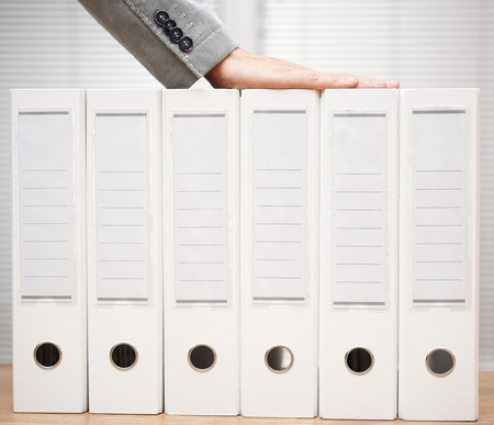 businessman holding organized documentation in binders, accounting services  and bookkeeping concept