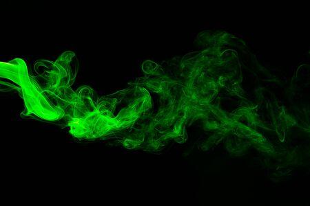 Green coloured smoke abstract lighting on a black background Фото со стока