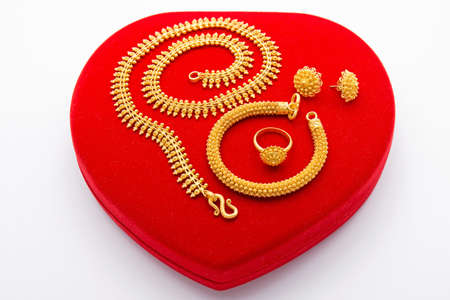 Precious Golden Jewelry Collection on Red Heart Box Stock Photo