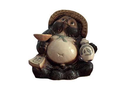 Estatua de Tanuki con la botella del motivo aislada en el fondo blanco