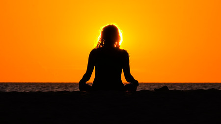meditating woman: Silhouette of meditating woman sitting in front of the red sinking sun on the beach Stock Photo