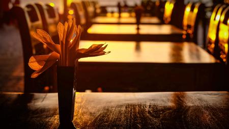 serviettes: Serviettes in a napkin holder standing on a dark wood table in an empty restaurant with emptydark wood chairs Stock Photo
