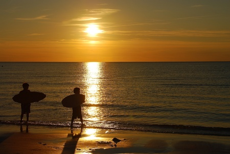 boarders: Skim boarders in Orleans, Mass at sunset.