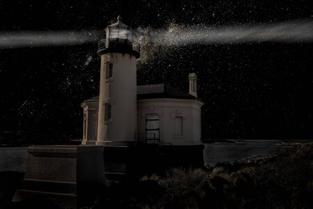 A Lighthouse shines through the night under a starry black sky. Color image.