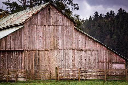 Een oude schuur op een landelijke boerderij met bomen, lucht en wolken.