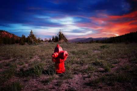 A red fire hydrant in the middle of a field with a colorful sunset in the background.
