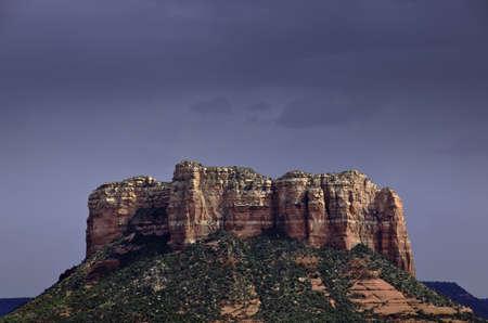 Dark gray sky over sunlit rocks near Sedona in Arizona photo