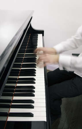 concerto: Piano keyboard with rapidly moving hands of the pianist appearing ghostly Stock Photo