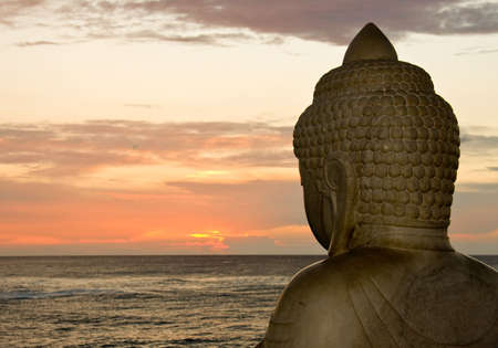 Side view of Buddha overlooking the setting sun photo