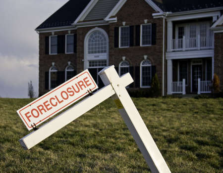 Modern house with crooked foreclosure sign in suburbs