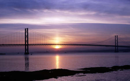 Forth Road Bridge near Edinburgh at sunset with the sun reflected in the River Forth photo