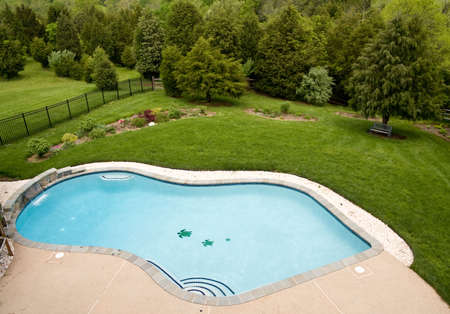 View of luxury pool and deck with surrounding landscaped garden with flowers and trees Stock Photo - 3042673