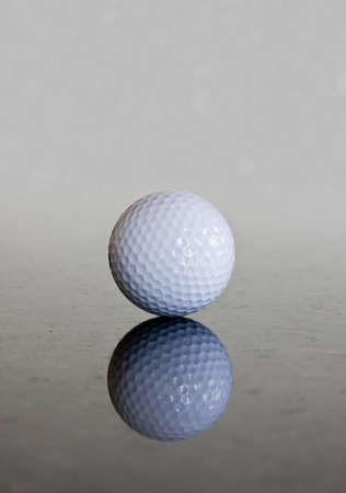 smooth: Single golf ball reflecting off a shiny marble surface Stock Photo