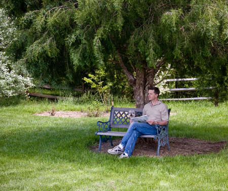 Middle aged man and a small puppy relax with a newspaper under a shady tree Stock Photo - 3068434
