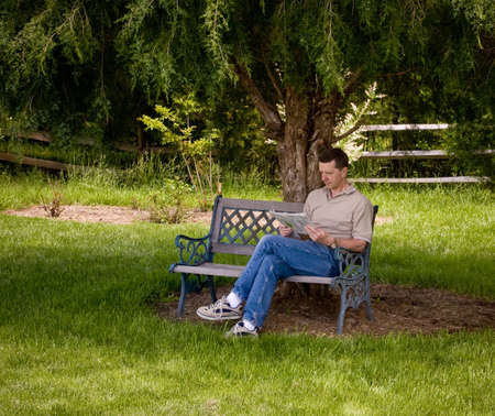 Man sitting on a garden bench reading a newspaper under the shade of a pine tree