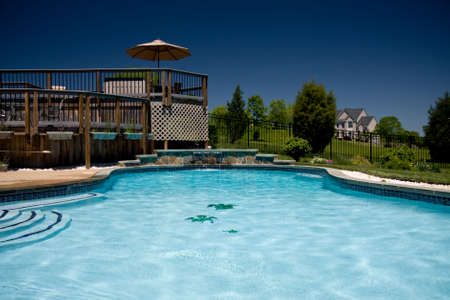 View of a backyard swimming pool with a deck taken from the water level