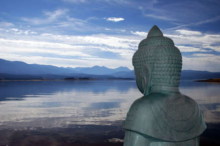 Backview of Buddha statue overlooking a peaceful mountain lake Stock Photo - 3181477