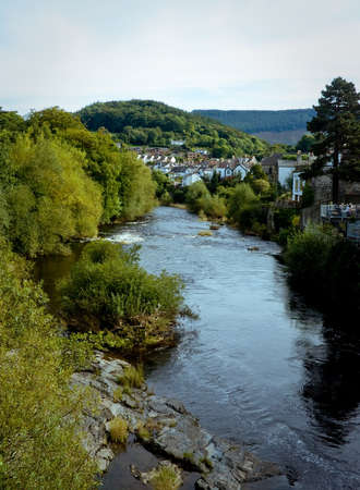 riverside tree: Vertical view of the river in Llangollen in Wales with the town and hills in the background Stock Photo