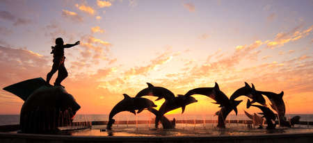 Statues of Dolphins in fountain in front of bright orange sunset over the ocean photo