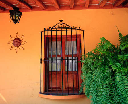Old fashioned stucco wall with window, grille, sun design and lamp