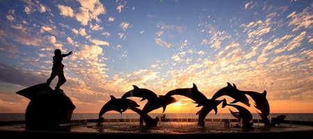 Dolphin statue in Mazatlan frames a beautiful sunset over the ocean photo