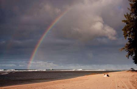 虹は、フォア グラウンドでカップルと砂浜 写真素材 - 4255641