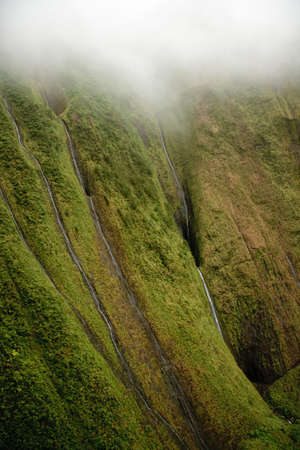 Several waterfalls streaming down the rock face in Kauai photo