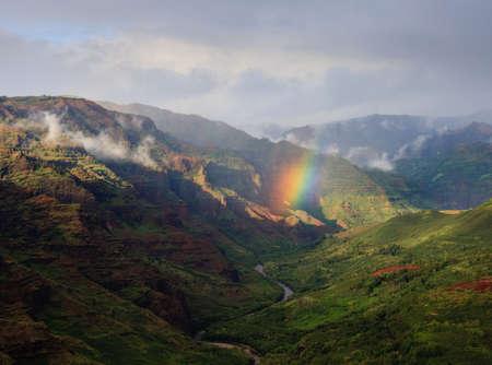 kauai: Rainbow in the center of the river valley of Waimea Canyon on Kauai Stock Photo