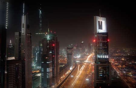 towering: Towering city skyscraper blocks in Dubai with view of Burj Stock Photo