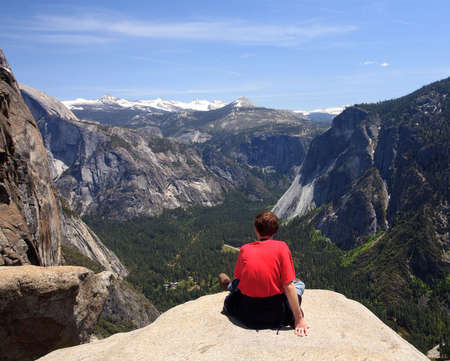 Rear view of young male hiker overlooking the distant snow covered mountains of the Sierra Stock Photo - 4924223