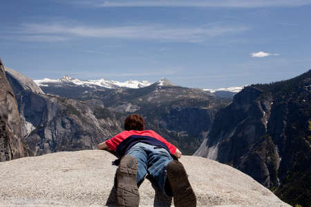 viewpoint: Male hiker at viewpoint at top of Yosemite falls overlooking distant mountains