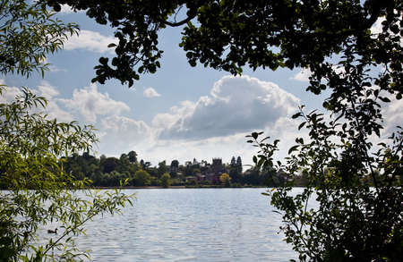 View of Ellesmere and lake framed by leaves of trees photo
