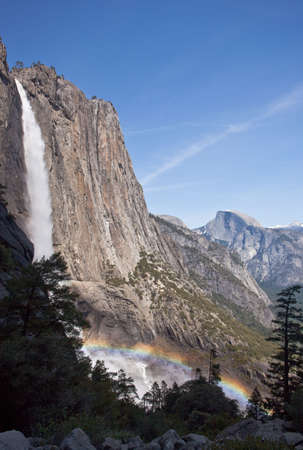 Rainbow forming over the spray from Yosemite falls with Half Dome in the background Stock Photo - 5300260
