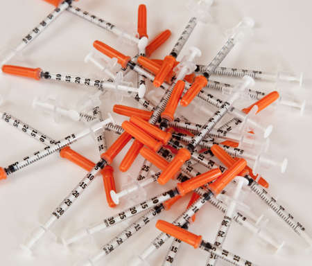 Pile of orange tipped hypodermic needles photo
