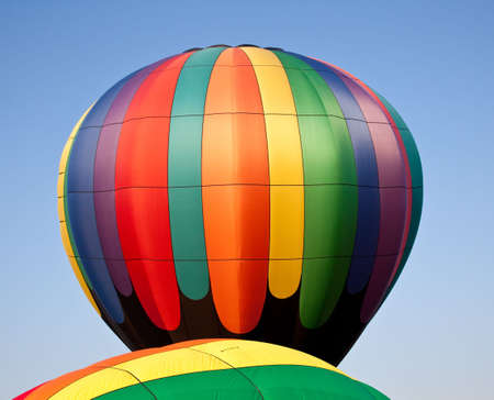 Colorful hot air balloon rising into the air above the canopy of another photo