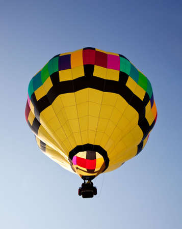 Yellow hot air balloon soaring skyward towards the sun Stock Photo