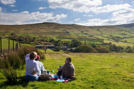 Vistas de las montañas lejanas con tres personas a tener un picnic en un campo