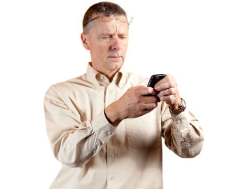 Senior businessman looking at phone with spectacles on forehead photo