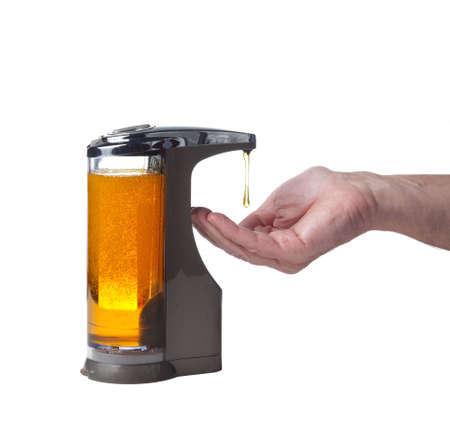 Soap or detergent being dispensed into male hand prior to hand washing Stock Photo